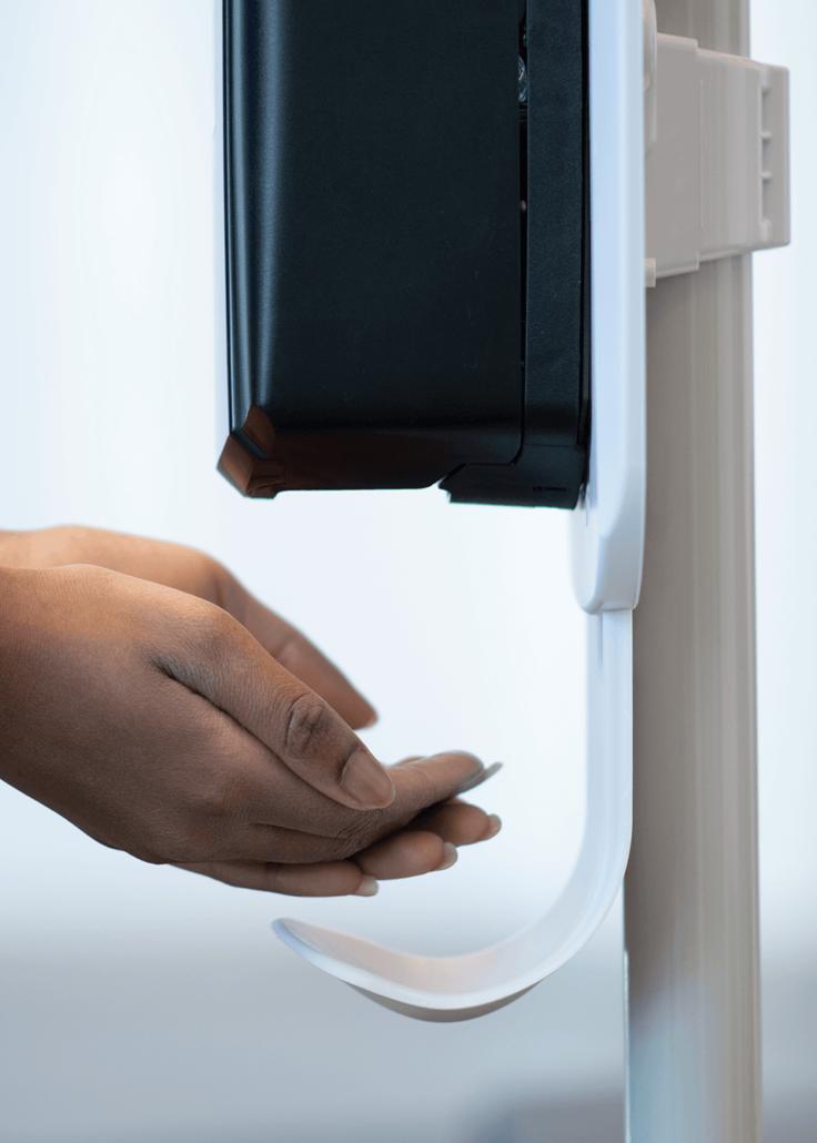Woman using a hand sanitiser dispenser
